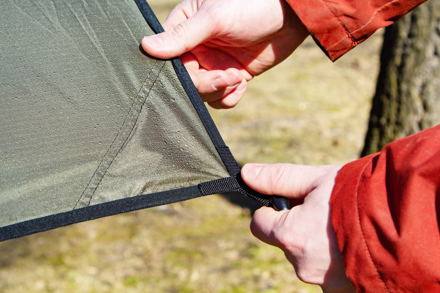 Close-up of male hands and the corner of an tarp with a grommet