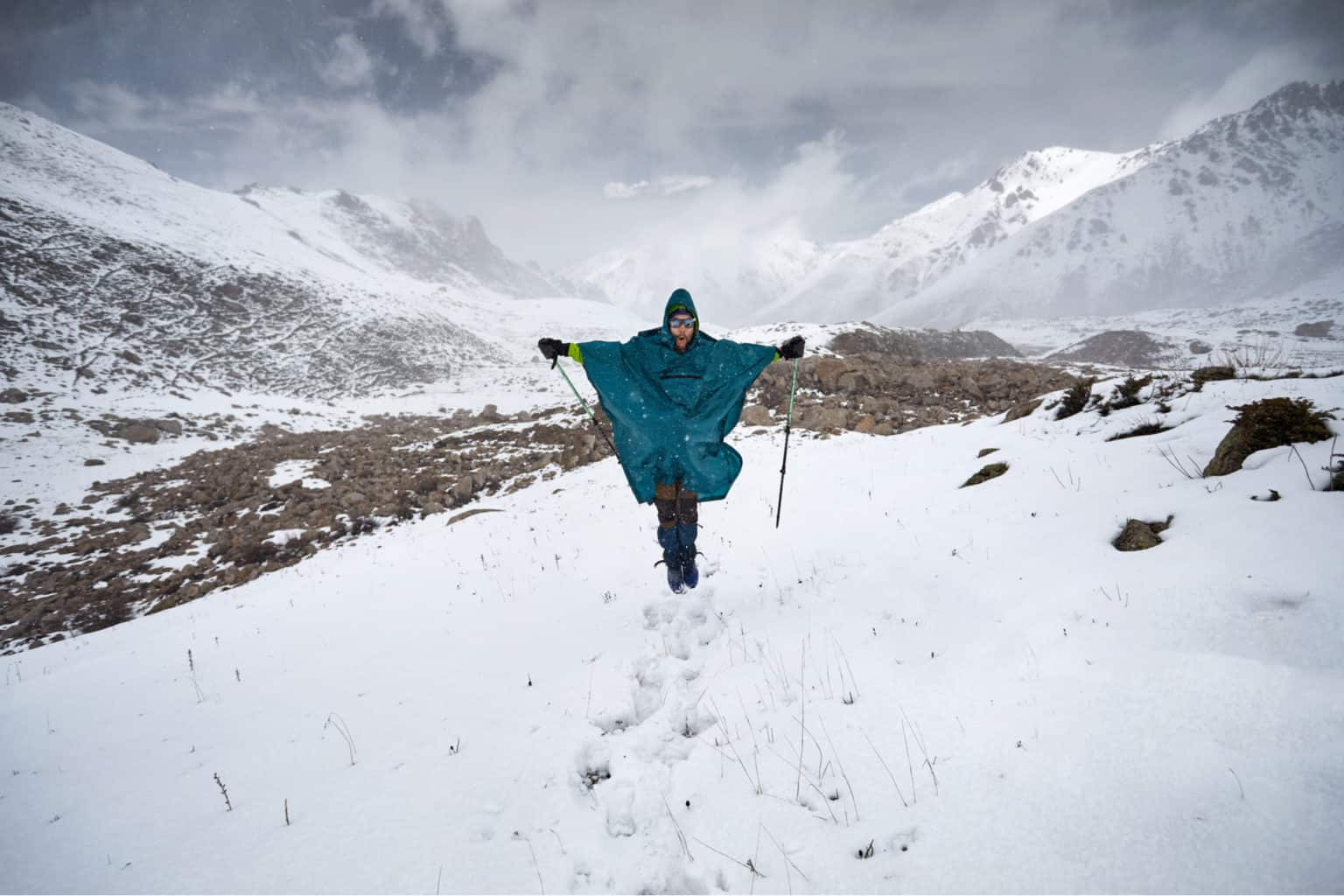 Hiker in blue raincoat poncho