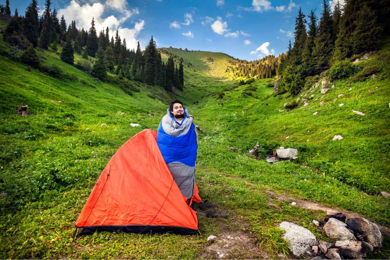 Man in sleeping bag next to orange tent