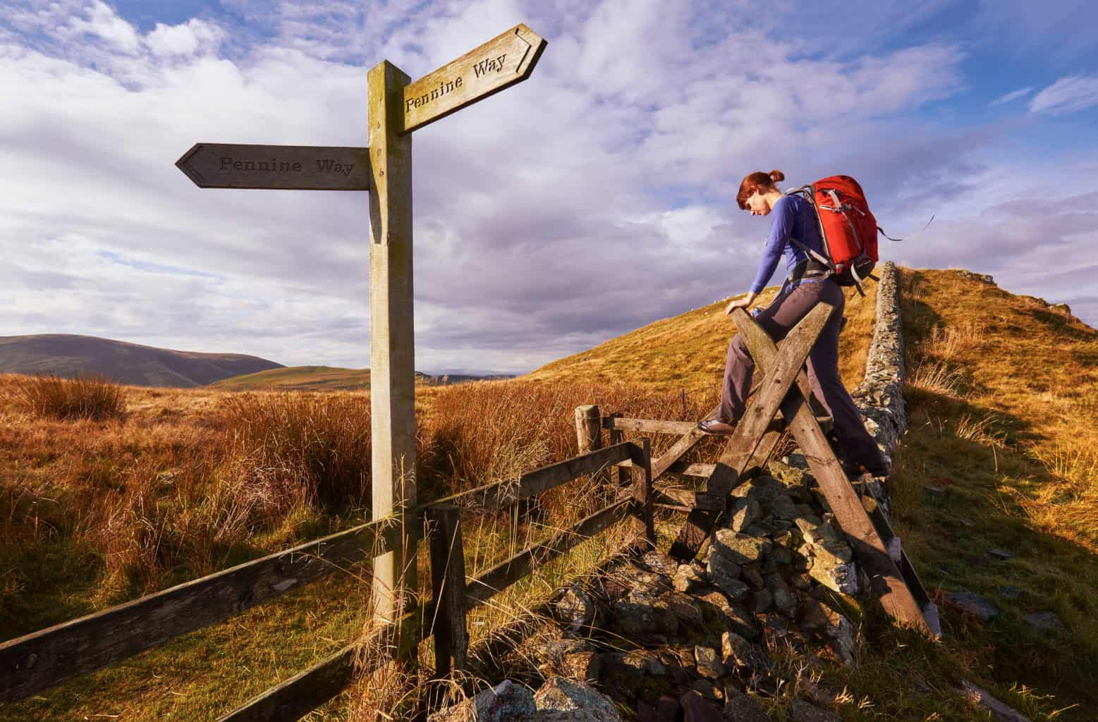 Woman crossing a stile on the Pennine way