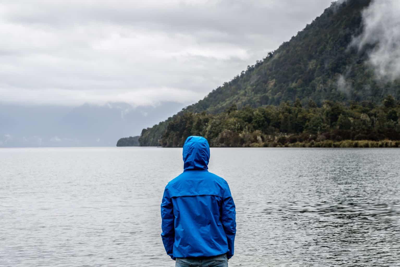 man standing by a lake wearing blue windbreaker