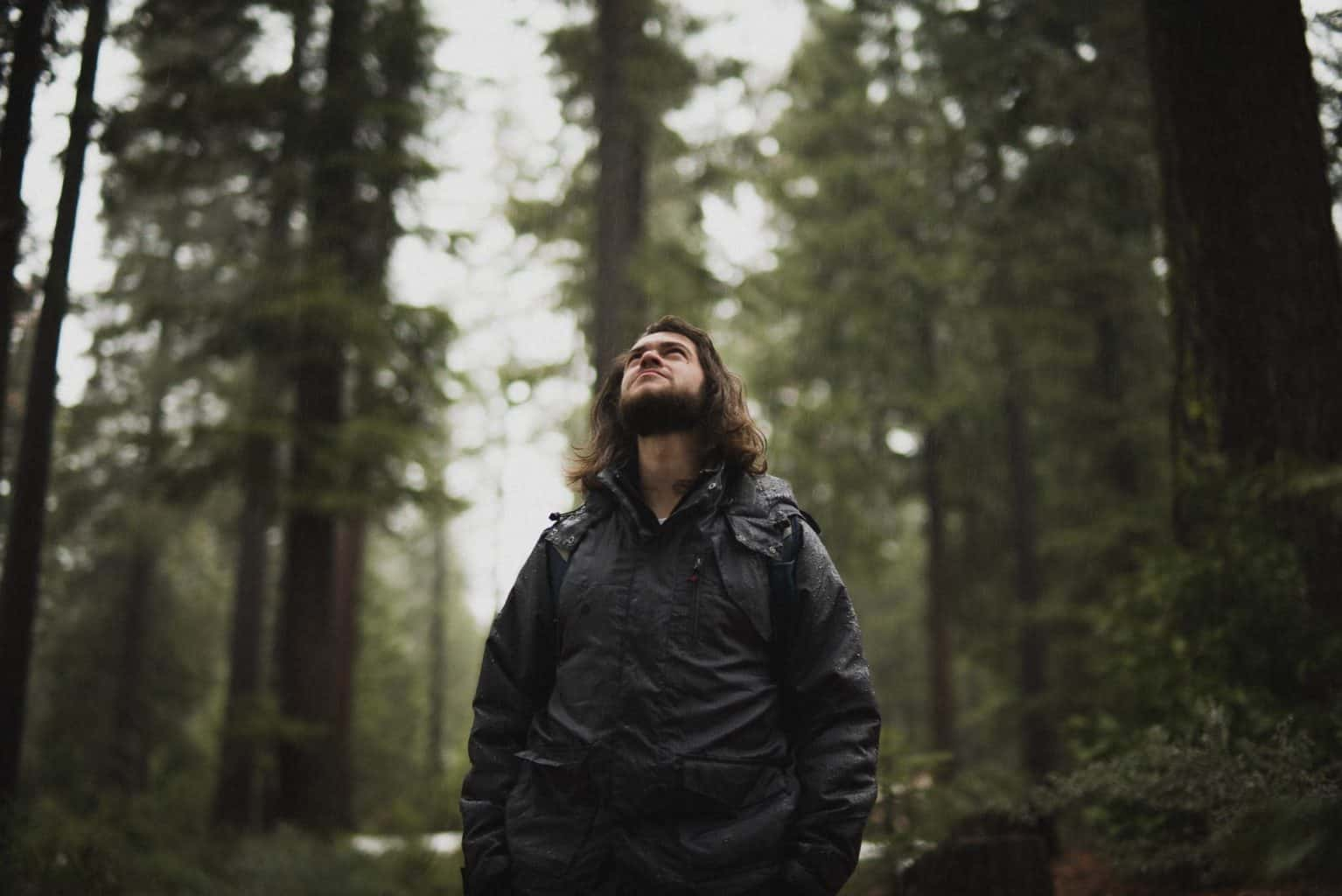 man standing in the forest in the rain