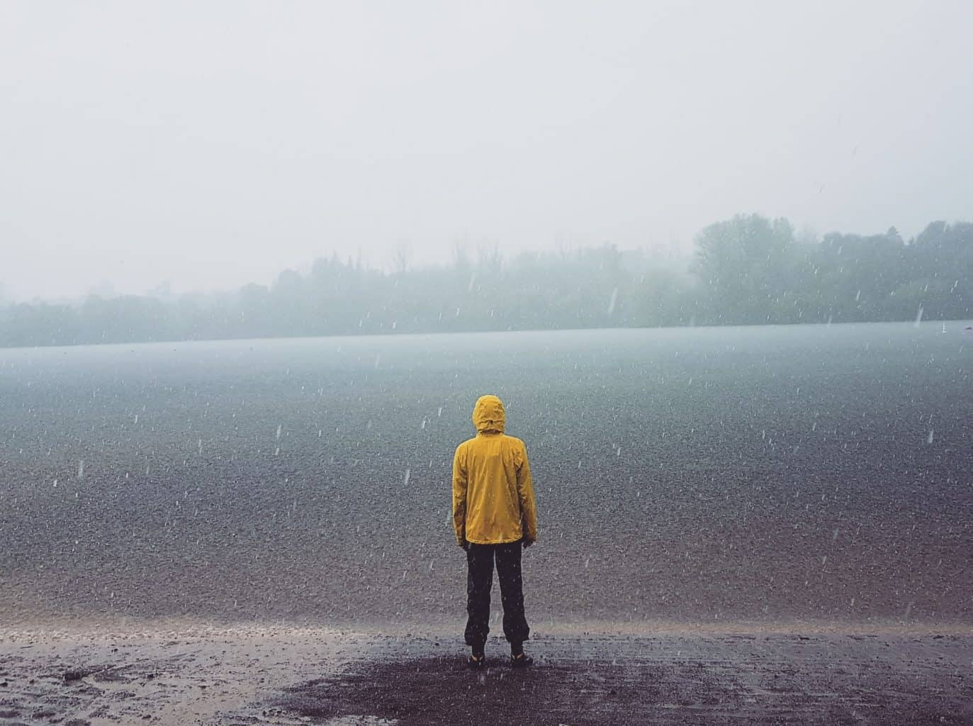 man wearing yellow rain jacket in the rain