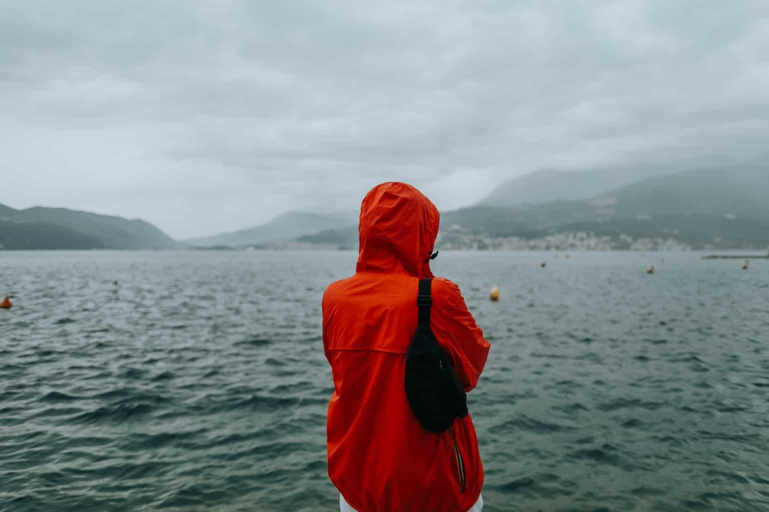 person standing by a lake wearing a red windbreaker