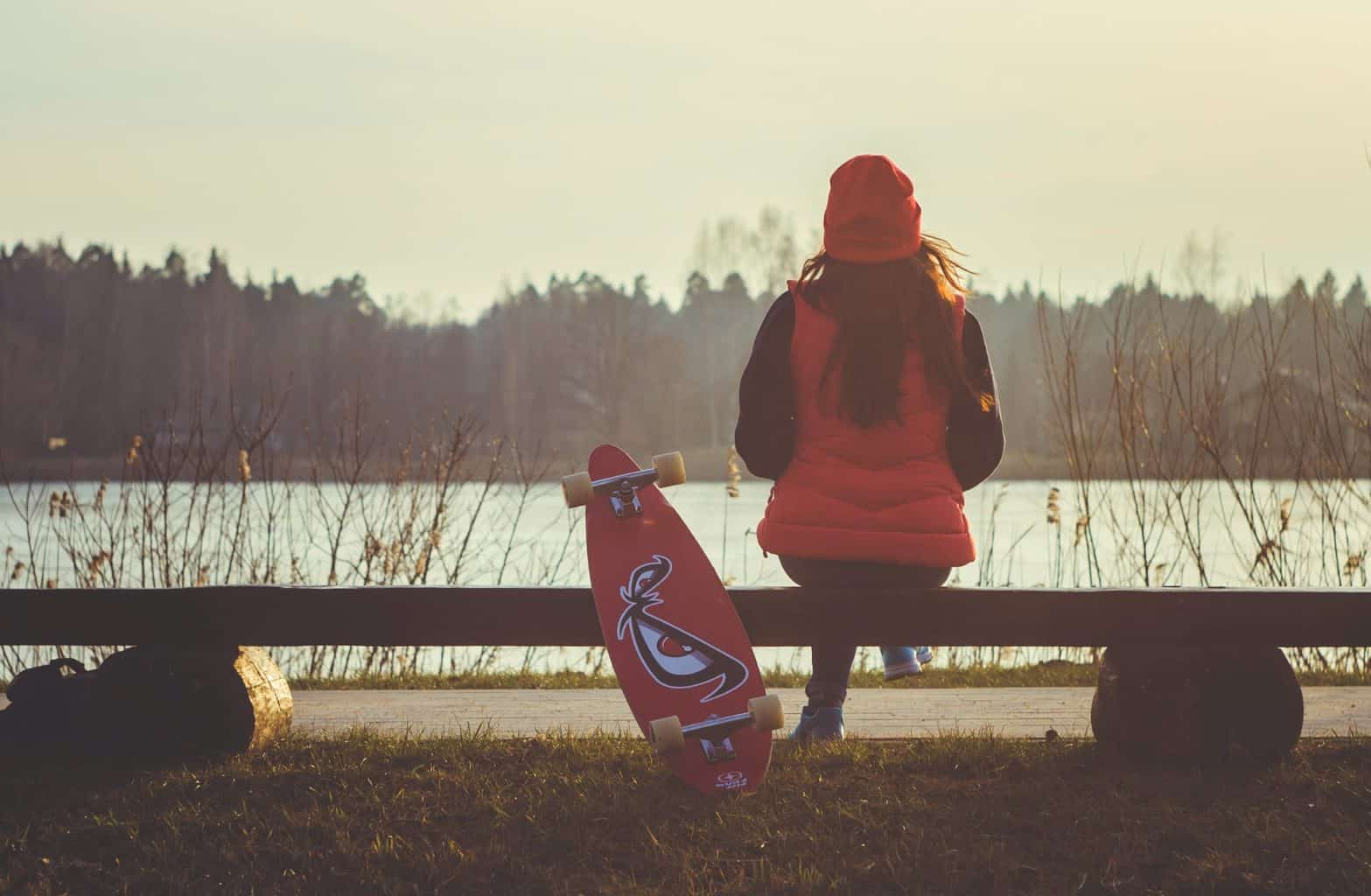 woman sitting on bench wearing red down jacket