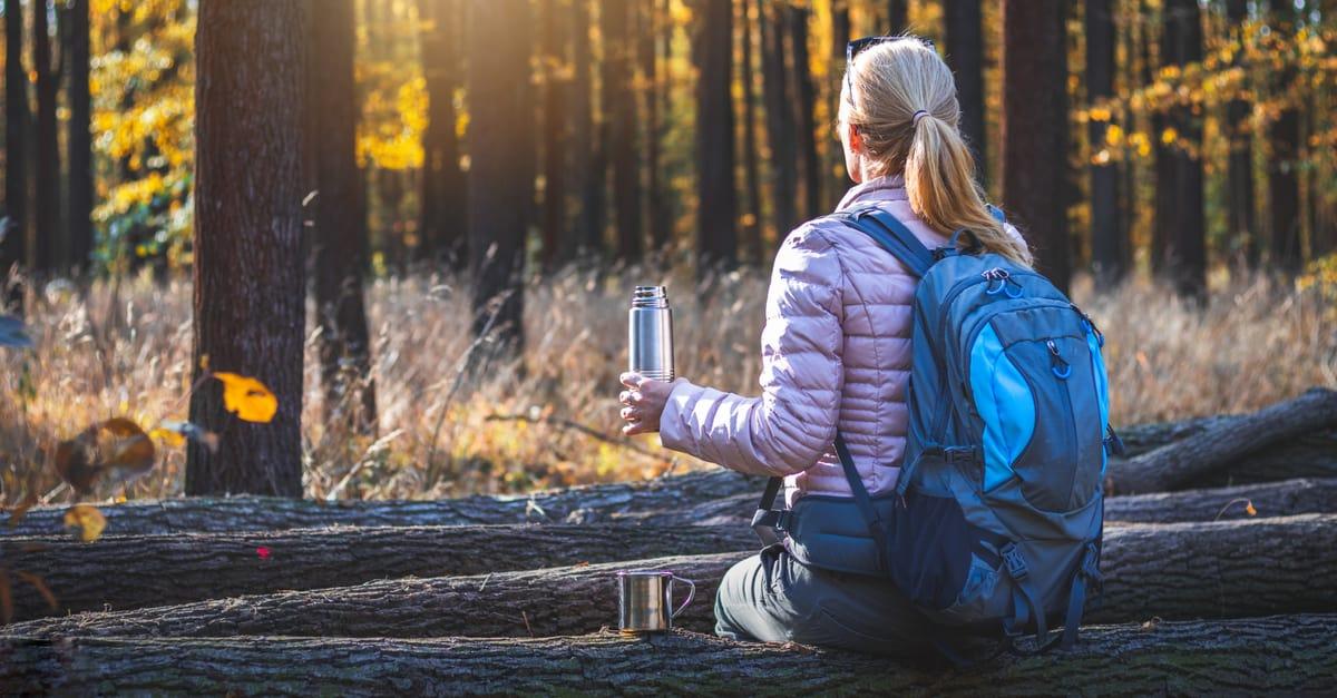 Female hiker holding a stainless steel bottle