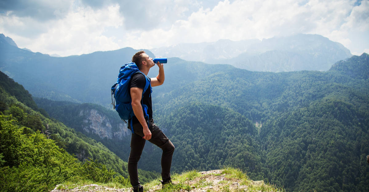 Hiker drinking out of a bottle