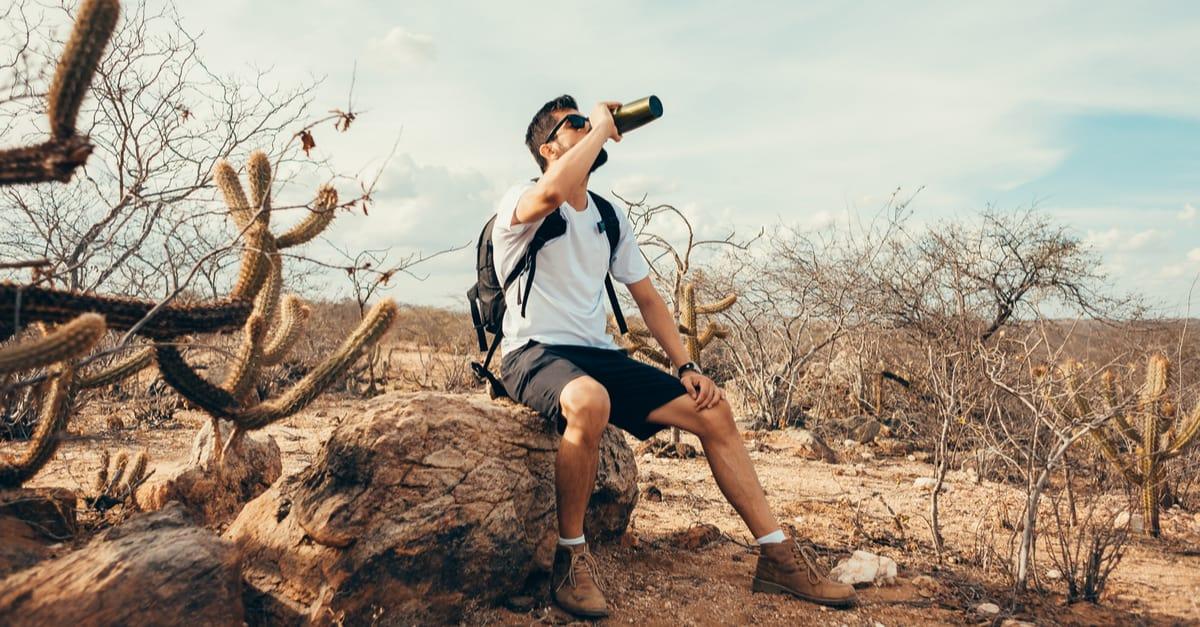 Hiker drinks out of a black bottle